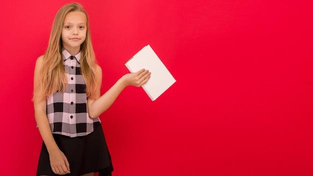 Linda menina com roupas de verão, isolada sobre um fundo vermelho, segurando um livro - imagem
