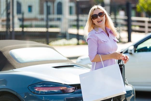 Linda menina com sacolas de compras perto de um carro dela
