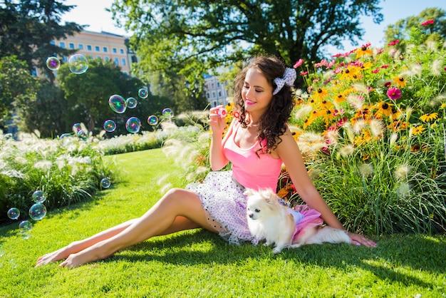 Linda menina com um cachorro pequeno chihuahua no parque