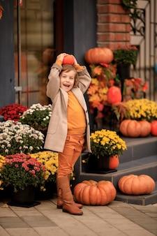 Linda menina com um chapéu na escada da casa com abóboras e flores