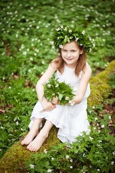 Linda menina com um vestido branco caminha na floresta de primavera. retrato da menina bonita com uma coroa de flores da primavera na cabeça.