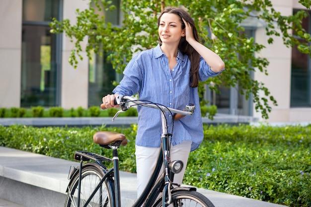Linda menina com uma bicicleta na estrada