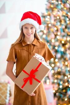 Linda menina com uma caixa de presente perto da árvore de natal. feliz natal e boas festas.