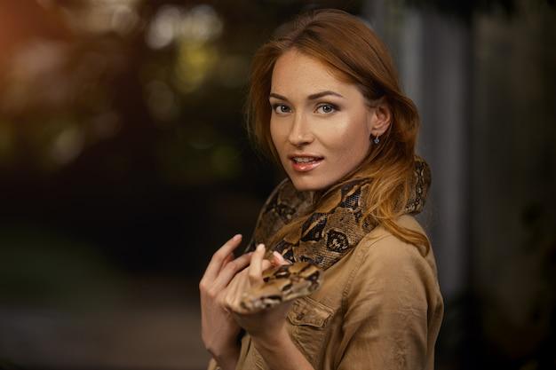 Linda menina com uma python nos ombros