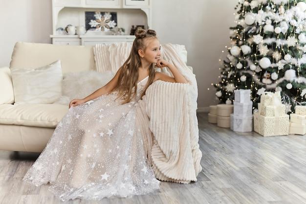 Linda menina com vestido festivo no interior de natal