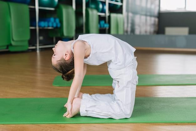 Linda menina criança praticando camelo pose no ginásio