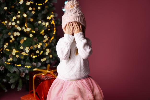 Linda menina de chapéu esperando surpresa perto de presentes e árvore de natal