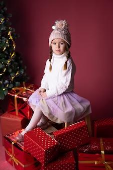 Linda menina de chapéu, sentado perto de presentes e árvore de natal