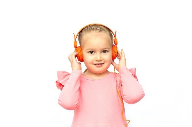 Linda menina de cinco anos usando fones de ouvido e ouvindo sua música favorita