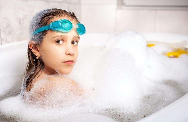 Linda menina de olhos azuis com óculos de natação tomando banho de espuma