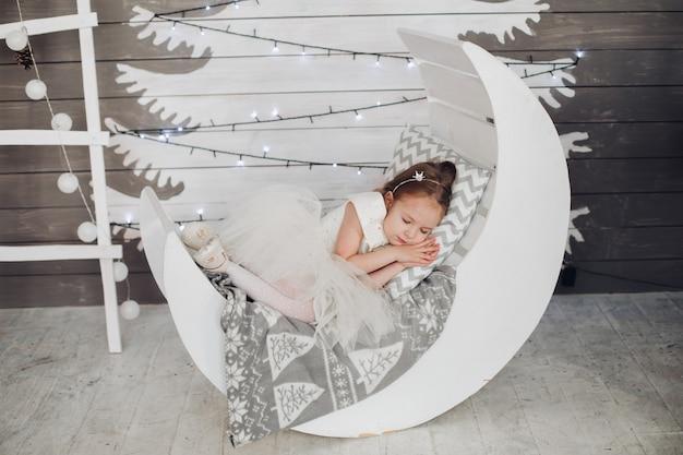 Linda menina dormindo na cama contra a árvore de natal pintada.