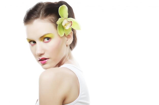 Linda menina elegante com flor de orquídea no cabelo.