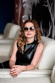 Linda menina elegante em vestido de couro e óculos.