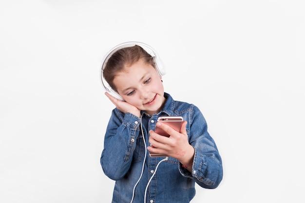 Linda menina em fones de ouvido navegando smarthone
