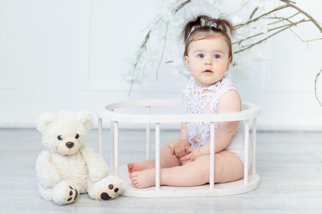 Linda menina em um macacão branco com um ursinho de pelúcia