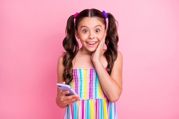 Linda menina engraçada duas caudas encaracoladas fofas segurando o telefone