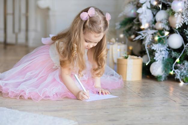 Linda menina escrevendo carta para o papai noel na véspera de ano novo. criança bonita está pensando debaixo da árvore de natal.