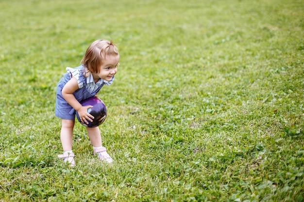 Linda menina feliz brincando com uma bola em um prado verde na natureza no parque