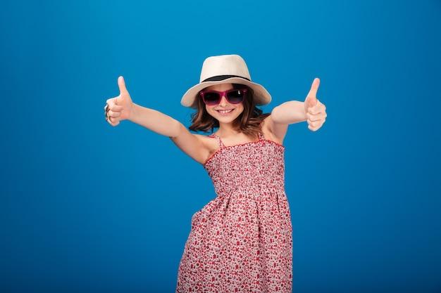 Linda menina feliz com chapéu e óculos escuros mostrando os polegares para cima com as duas mãos sobre o fundo azul