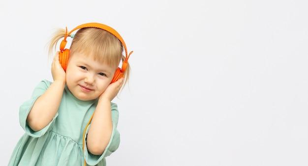 Linda menina feliz e fofa com fones de ouvido