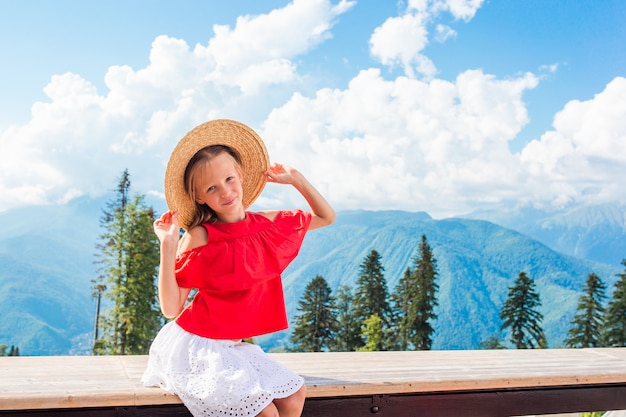 Linda menina feliz nas montanhas no fundo do nevoeiro