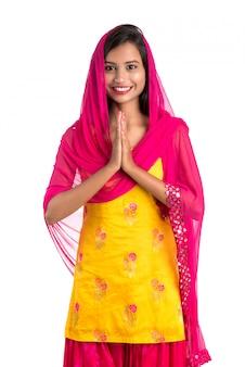 Linda menina indiana com expressão de boas-vindas (convidando), cumprimentando namaste.