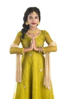 Linda menina indiana com expressão de boas-vindas (convidativa), cumprimentando namaste