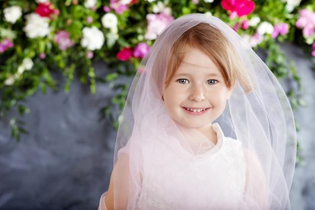 Linda menina joga contra as flores. retrato da menina muito sorridente
