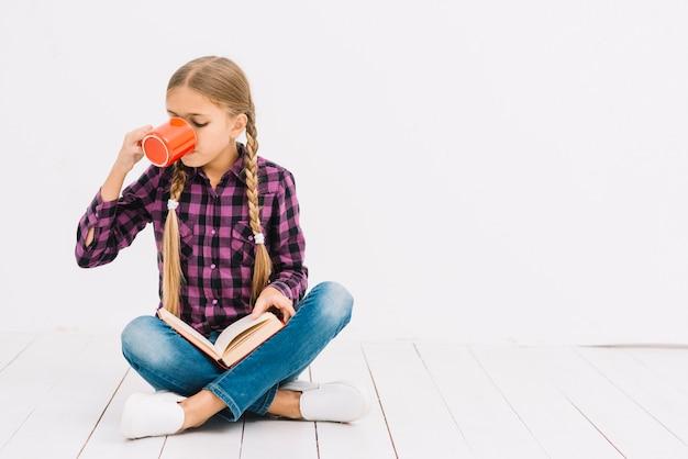 Linda menina lendo um livro e segurando uma caneca