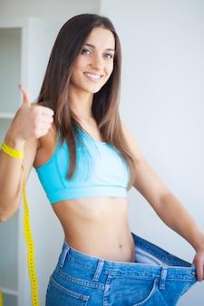 Linda menina magro alegre mostrando o resultado da dieta