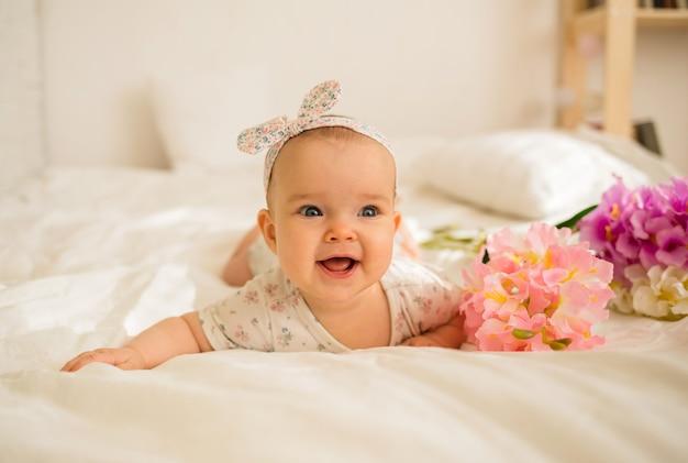 Linda menina mentindo e sorrindo com flores na cama