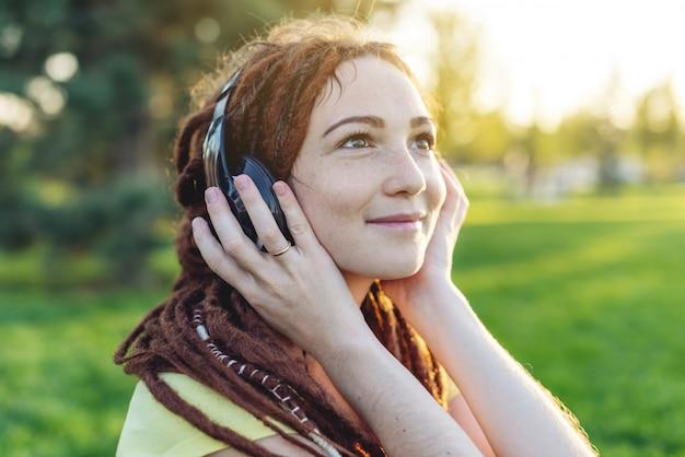 Linda menina moderna com dreadlocks ouvindo música com fones de ouvido no outono sunny park