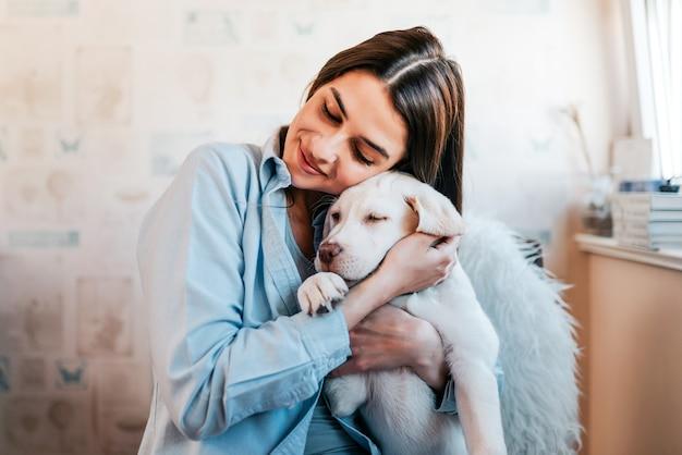 Linda menina morena abraçando seu cachorro em casa. fechar-se.