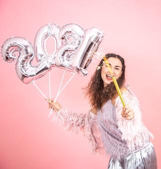 Linda menina morena alegre vestida de maneira festiva com cabelo encaracolado, posando em um fundo rosa de estúdio com balões de prata para o conceito de ano novo