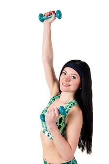 Linda menina morena com cabelos longos é treinada com halteres azuis.
