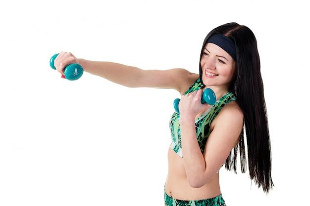 Linda menina morena com cabelos longos é treinada de boxe com halteres.