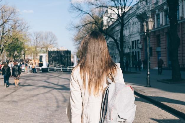Linda menina morena com cabelos longos no casaco percorre a cidade na primavera
