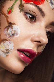 Linda menina morena com cachos e um padrão floral na face. flores de beleza.