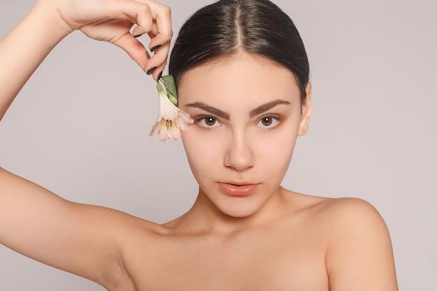 Linda menina morena com olhos verdes maquiagem e pele fresca posando em um fundo vermelho com flor, conceito de cuidados com a pele, spa de beleza, produto bio. horizontal