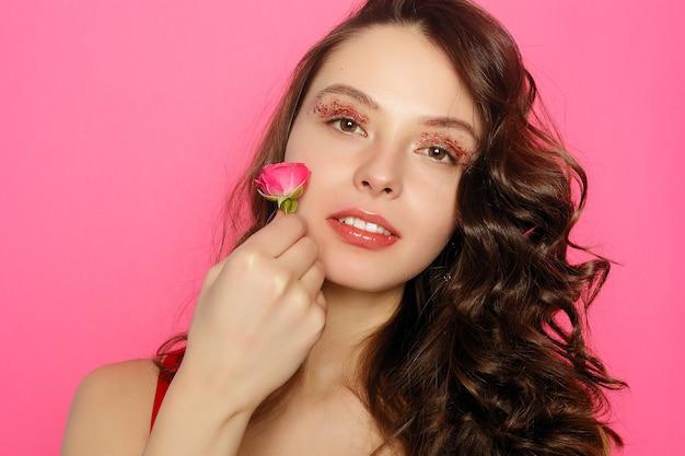 Linda menina morena com olhos verdes maquiagem e pele fresca posando no fundo rosa com flor, conceito de cuidados com a pele, spa de beleza, produto bio. horizontal