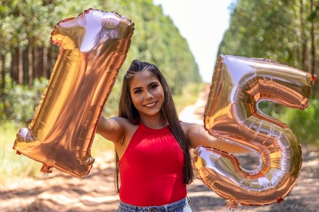 Linda menina morena comemorando 15 anos de vida, debutante.