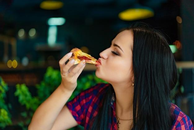Linda menina morena de camiseta, comer pizza no restaurante. uma garota bonita se sente feliz e gosta de comer um pedaço de pizza deliciosa.