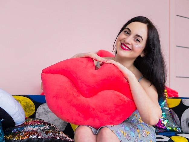Linda menina morena de vestido segurando grandes lábios vermelhos