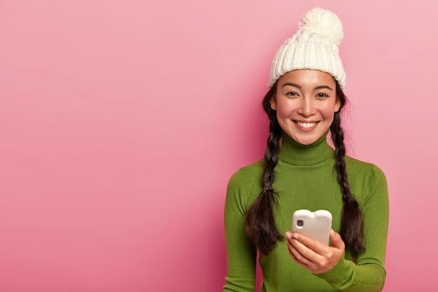 Linda menina morena disca um número de telefone, segura um smartphone moderno, conversa em redes sociais, envia mensagem, digita feedback para vídeo engraçado