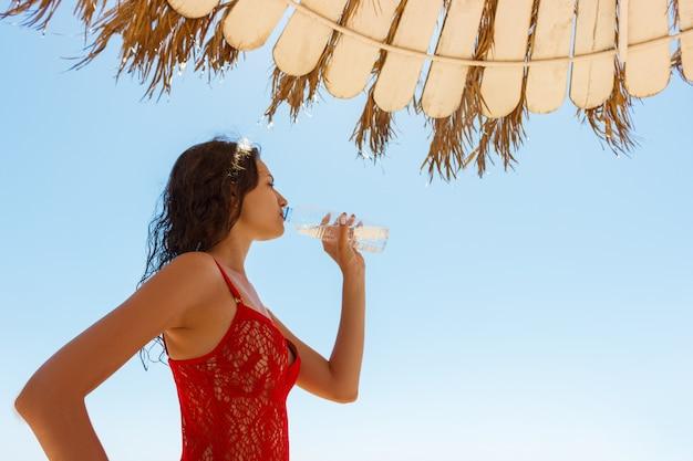 Linda menina morena em vermelho maiô bebendo água em um dia de férias