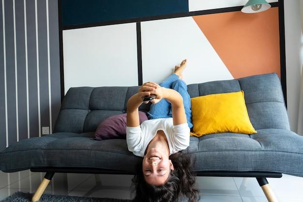 Linda menina morena entediada no sofá em um interior elegante está assistindo tv. muda o canal de tv com um controle remoto na mão