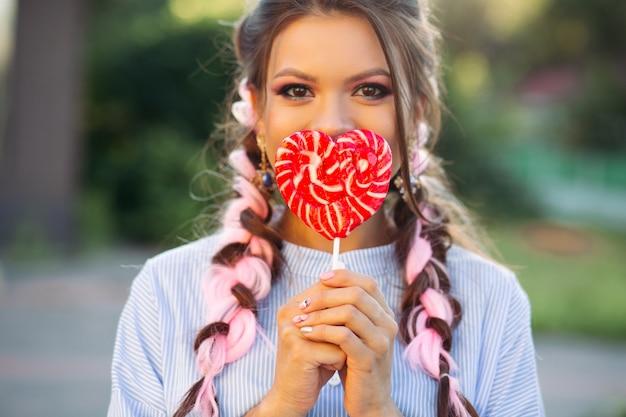 Linda menina morena, escondendo o rosto pelo coração de doces na vara.