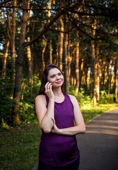 Linda menina morena falando ao telefone no parque ao pôr do sol
