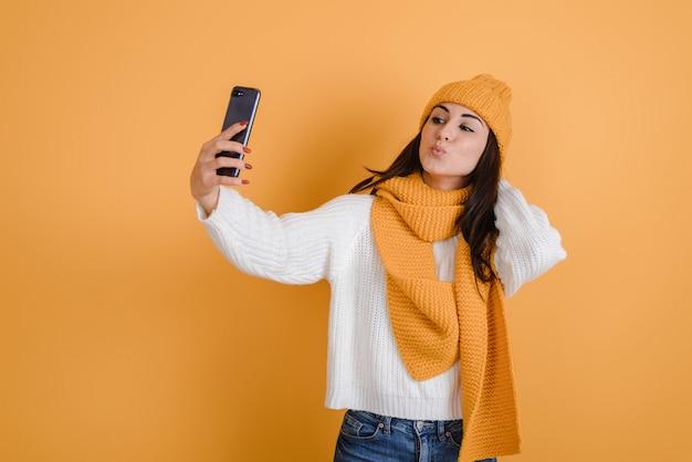 Linda menina morena faz selfies em estúdio, ela está de chapéu de malha e cachecol
