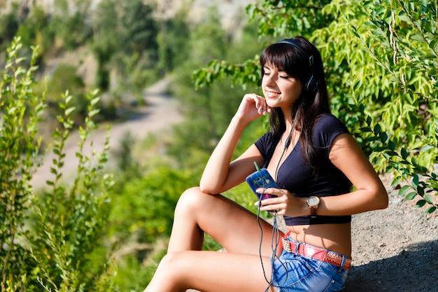 Linda menina morena ouvindo música ao ar livre